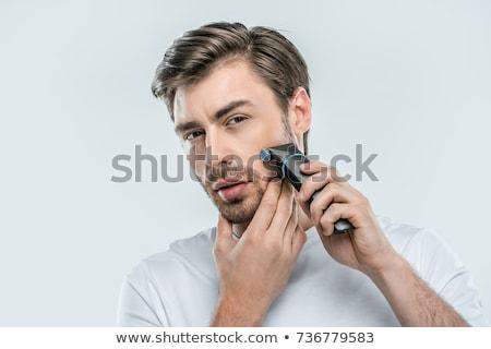 Fiatalember elektromos borotva fiatal jóképű férfi szürke Stock fotó © deandrobot