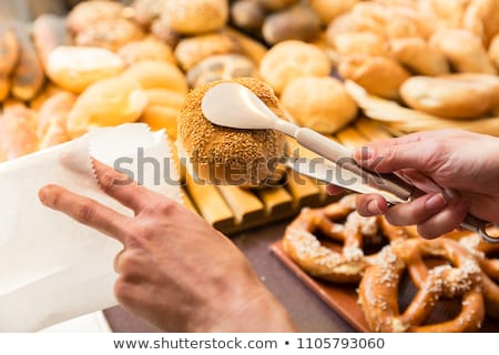 Sales woman in baker shop putting bread roll in paper bag Stock photo © Kzenon