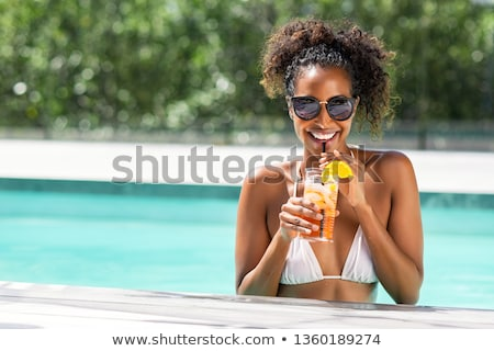 Stockfoto: Young Woman Standing With Cocktail By The Swimming Pool