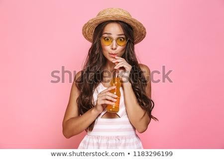 Photo of glamour woman 20s wearing sunglasses and straw hat drin Stock photo © deandrobot