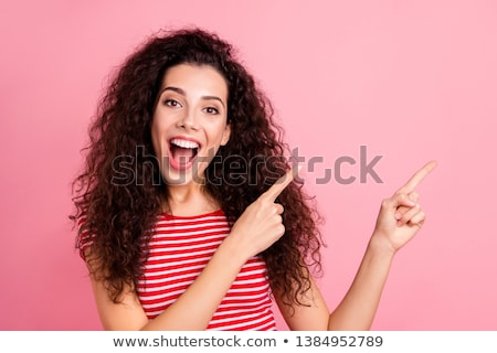 Image of two excited girls smiling and pointing fingers aside to Stock photo © deandrobot