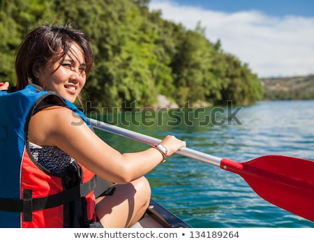 Pretty young woman in the canoe on the lake Stock photo © boggy