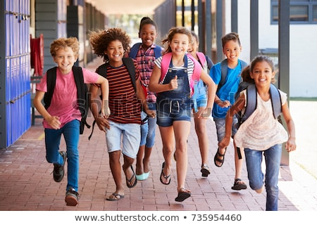 Front view of multi ethnic group of happy school kids playing tug of war in playground Stock photo © wavebreak_media