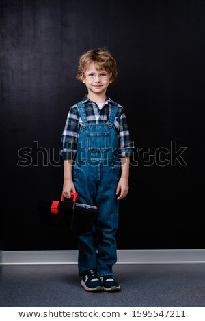 Happy little boy in denim overalls and eyeglasses holding toolbox Stock photo © pressmaster