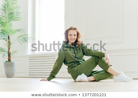 Happy fitness red haired woman leans with hand on floor, has time for rest after gymnastic exercises Stock photo © vkstudio