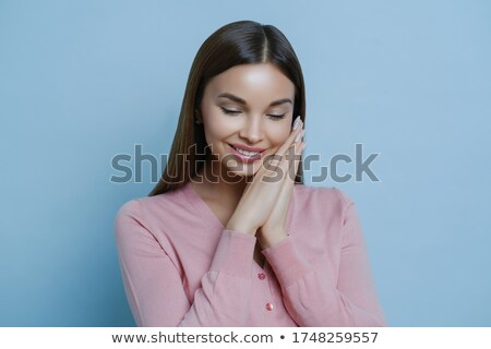 Portrait of glad shy woman keeps hands pressed together near face, concentrated down, pleased to hea Stock photo © vkstudio