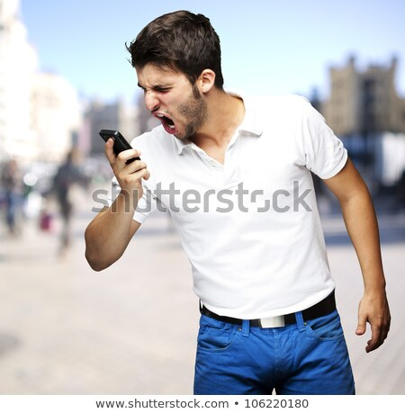 Angry young man shouting using mobile Stock photo © posterize