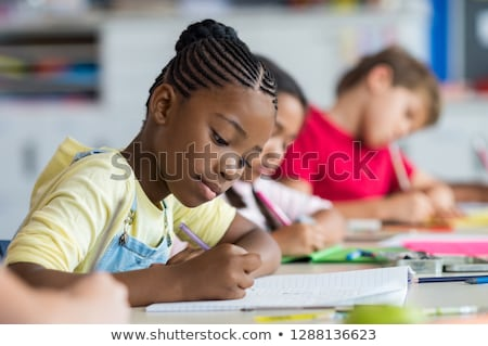 cute pupils writing at desk in classroom stock photo © wavebreak_media
