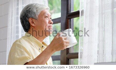 Man looking up while drinking morning coffee Stock photo © ozgur