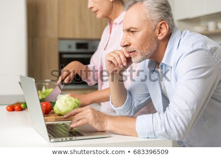 concentrated woman standing and cooking on the kitchen stock photo © deandrobot