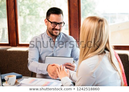 Couple holds hands across table and smiles Stock photo © dash