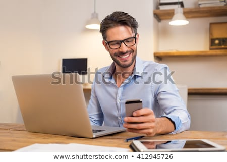 Businessman works with his smartphone in office Stock photo © alphaspirit