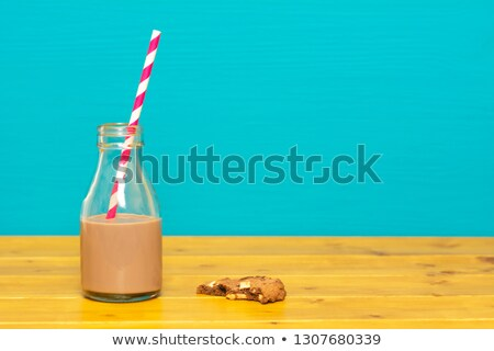 Bottle half full with chocolate milkshake with a half-eaten cook Stock photo © sarahdoow