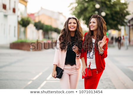 Laughing women in sport chic suits and handbags in the street. Stock photo © studiolucky