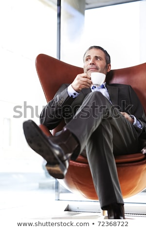 Business executive in red chair enjoying coffee.  Stock photo © lichtmeister
