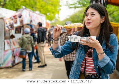 happy cute gilr eating street food and looking enjoyable in a traditional small fair BANNER, LONG FO Stock photo © galitskaya