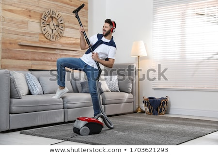 Adam kulaklık elektrikli süpürge ev ev temizlik Stok fotoğraf © dolgachov