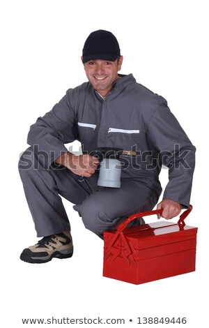 Stock photo: Man with blow-torch kneeling by tool kit