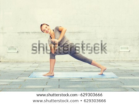 woman making yoga in twist pose on mat outdoors stock photo © dolgachov