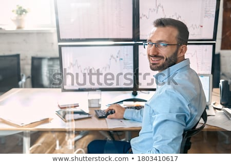 Business person sitting at desk with financial change concept Stock photo © ra2studio