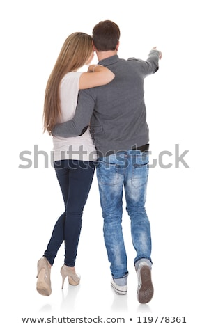 rear view of young couple holding hands and man pointing at horizon on beach in the sunshine stock photo © wavebreak_media