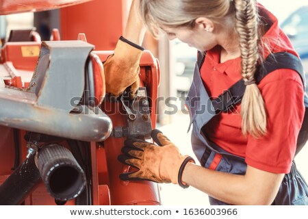 Woman machinist working with wrench of a farm machine Stock photo © Kzenon