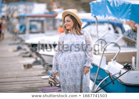 Tourist woman walks on wooden moor pier with touristic yachts Stock photo © ElenaBatkova