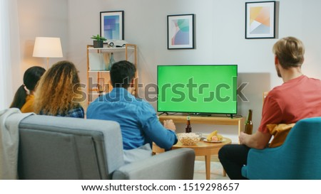 happy friends with drinks watching tv at home Stock photo © dolgachov
