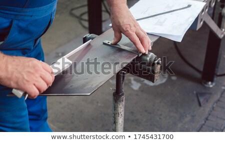 Metalworker measuring a strip of steel  Stock photo © Kzenon