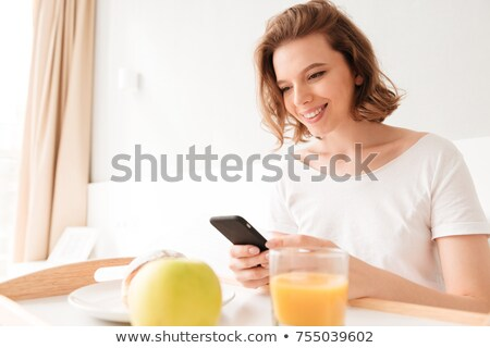 Portrait of a beautiful young lady sitting in the kitchen at home and smiling stock photo © maxpro