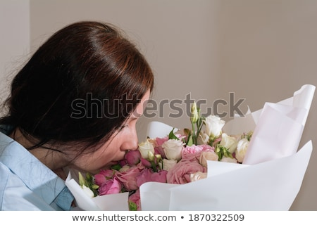 pretty brunette woman holding bunch of roses stock photo © hasloo