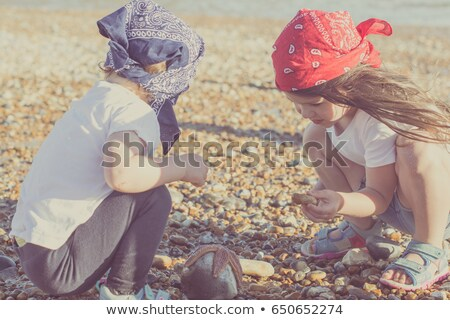 Two little girls is playing with pebble stones. focus on girl with white panama hat on her head. Stock photo © Paha_L