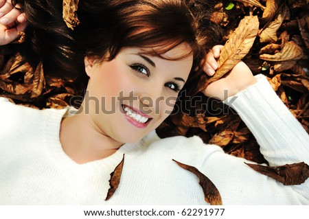 Young beauty girl laying on autumn ground and leaves, perfect face and natural skin, fashionable fal Stock photo © zurijeta