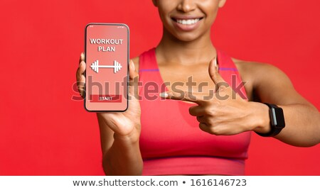 Fitness lady showing mobile phone display. Stock photo © deandrobot