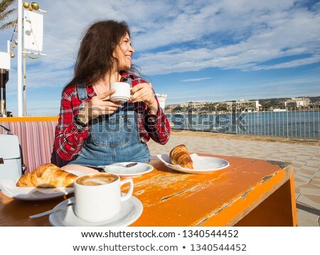 beautiful young woman drinking coffee and eating cake in cafe stock photo © deandrobot