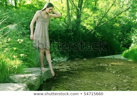 Girl dipping feet into stream Stock photo © IS2