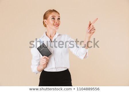 Young amazing business woman holding passport. Looking aside. Stock photo © deandrobot