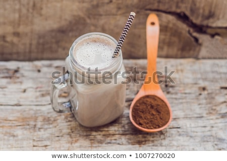 Drink from carob and kerob powder in a wooden spoon Stock photo © galitskaya