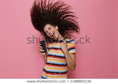 Gyönyörű nő pózol izolált rózsaszín hallgat zene Stock fotó © deandrobot