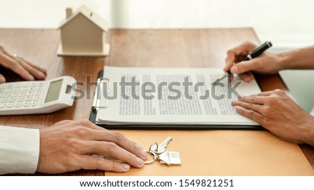 real estate developer agent and sign on document giving keys of stock photo © snowing