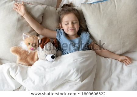 Little beautiful girl with light pillows in a cozy room. Stock photo © ElenaBatkova