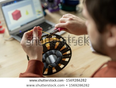 Hands of young designer with nippers cutting piece of yellow filament on spool Stock photo © pressmaster