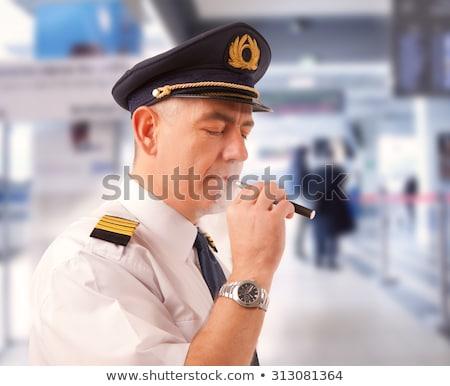 Légitársaság pilóta cigaretta visel egyenruha kalap Stock fotó © Amaviael