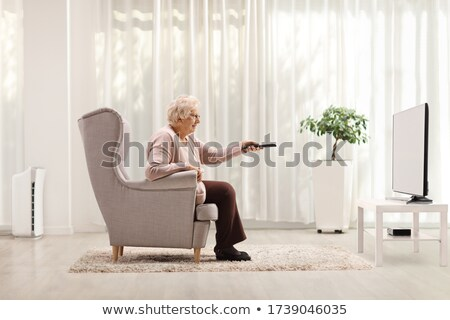 woman sitting on the couch with remote control stock photo © rastudio