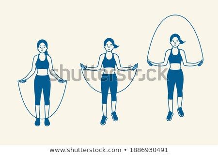 Full length image of fitness woman jumping with skipping rope Stock photo © deandrobot