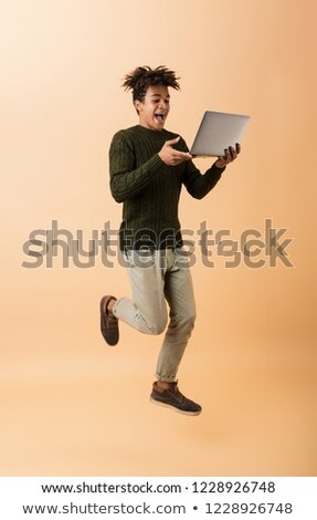 Full length photo of delighted african american guy wearing swea Stock photo © deandrobot