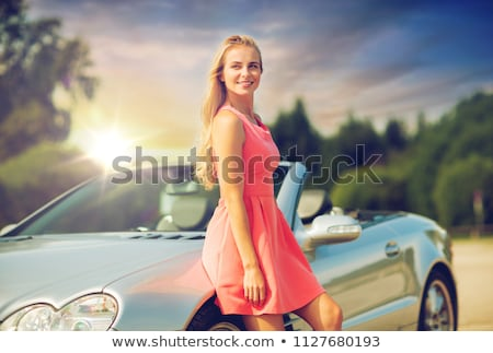 happy young woman in convertible car over sky Stock photo © dolgachov