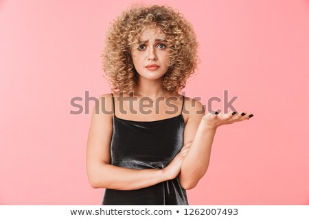 Portrait of displeased curly woman 20s wearing dress frowning wh Stock photo © deandrobot