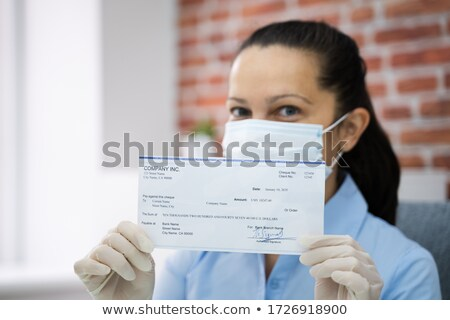 Woman In Face Mask Holding Paycheck Stock photo © AndreyPopov
