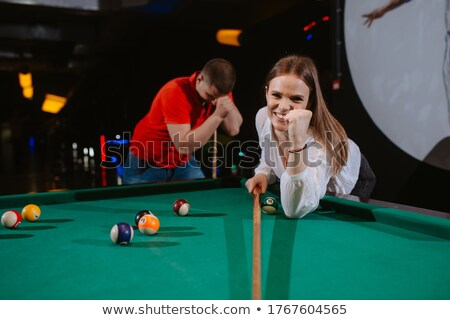 Young man concentrating while aiming at pool ball while playing  Stock photo © cozyta